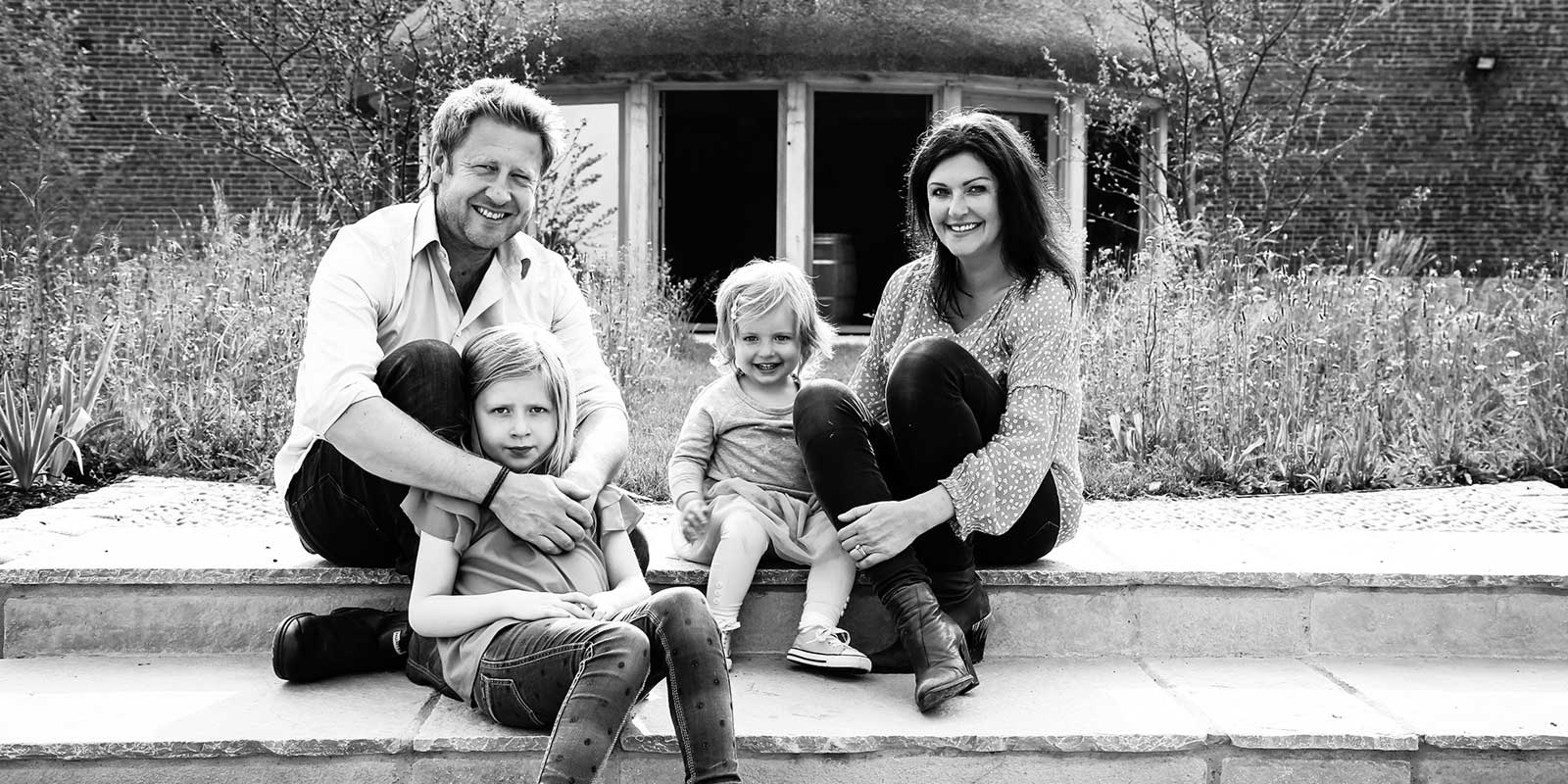 A family business, Jo, Matt and their two children sat in front of the round house