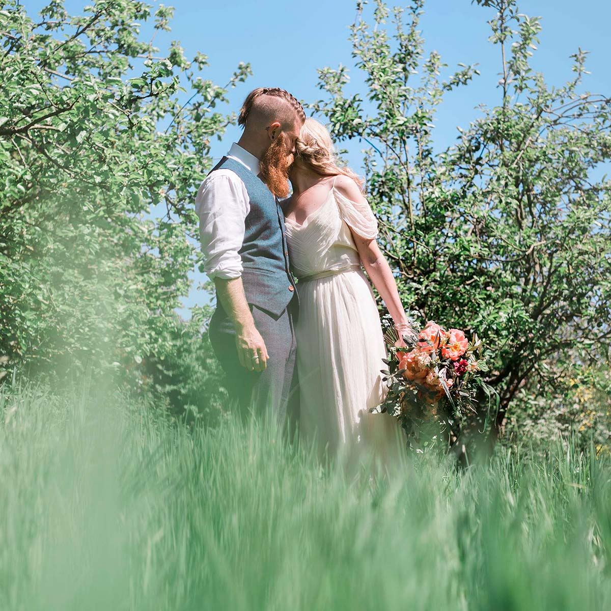Bride and groom embraced in wildflower meadow after their elopement wedding