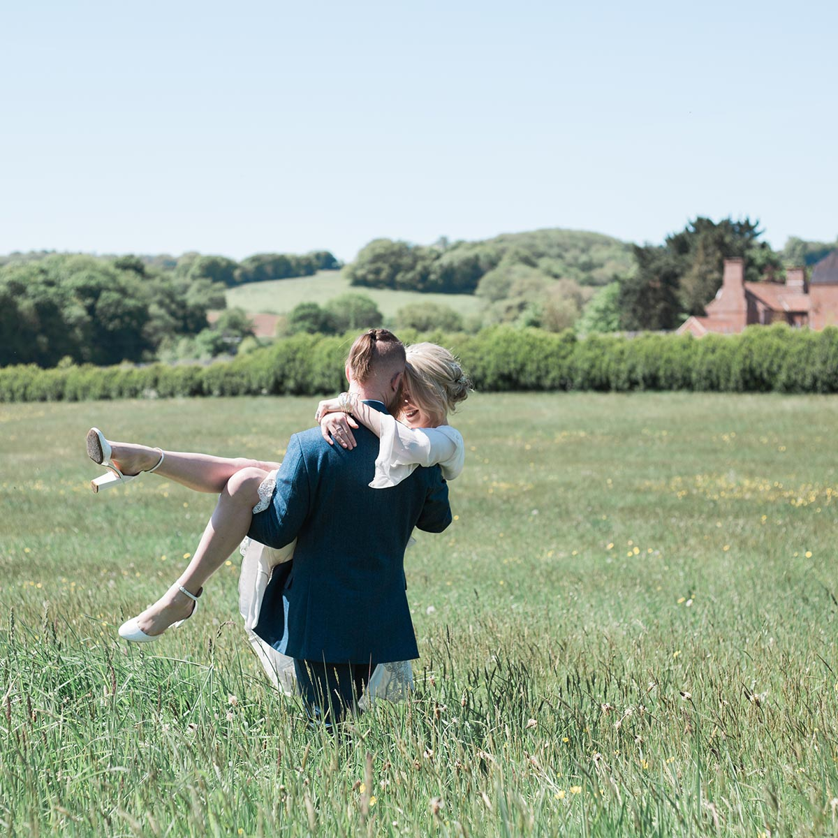 Runaway weddings - groom carrying bride in the wildflower hay meadow