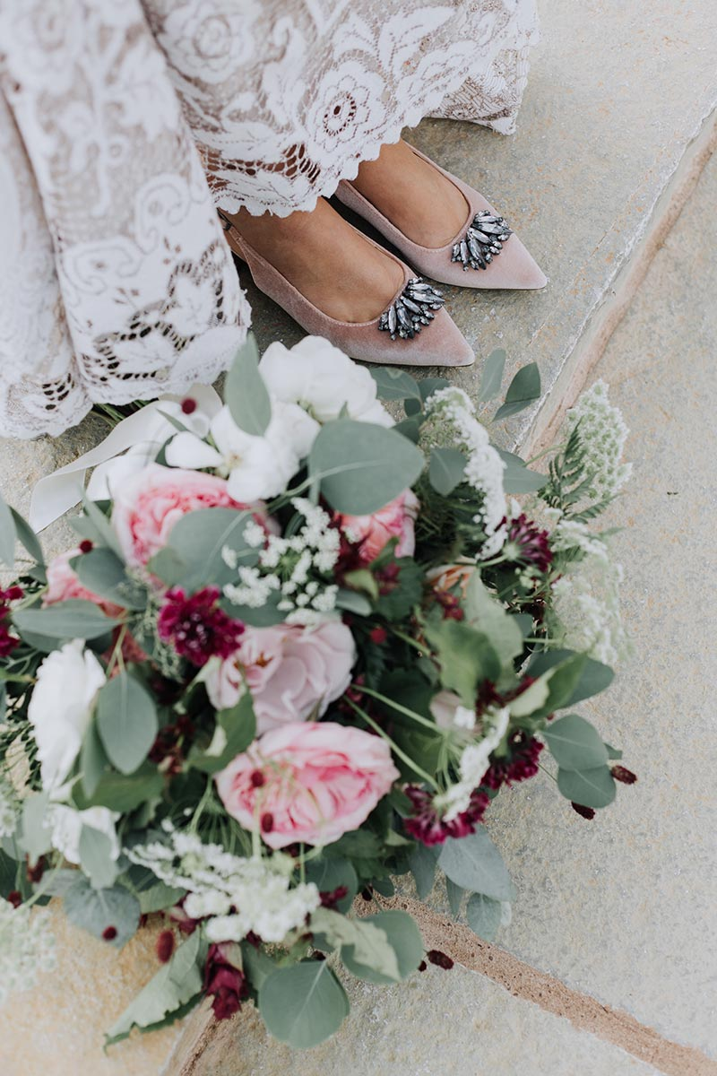Stunning wedding bouquet placed at feet of the bride