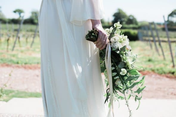 Bride holding bouquet in countryside setting