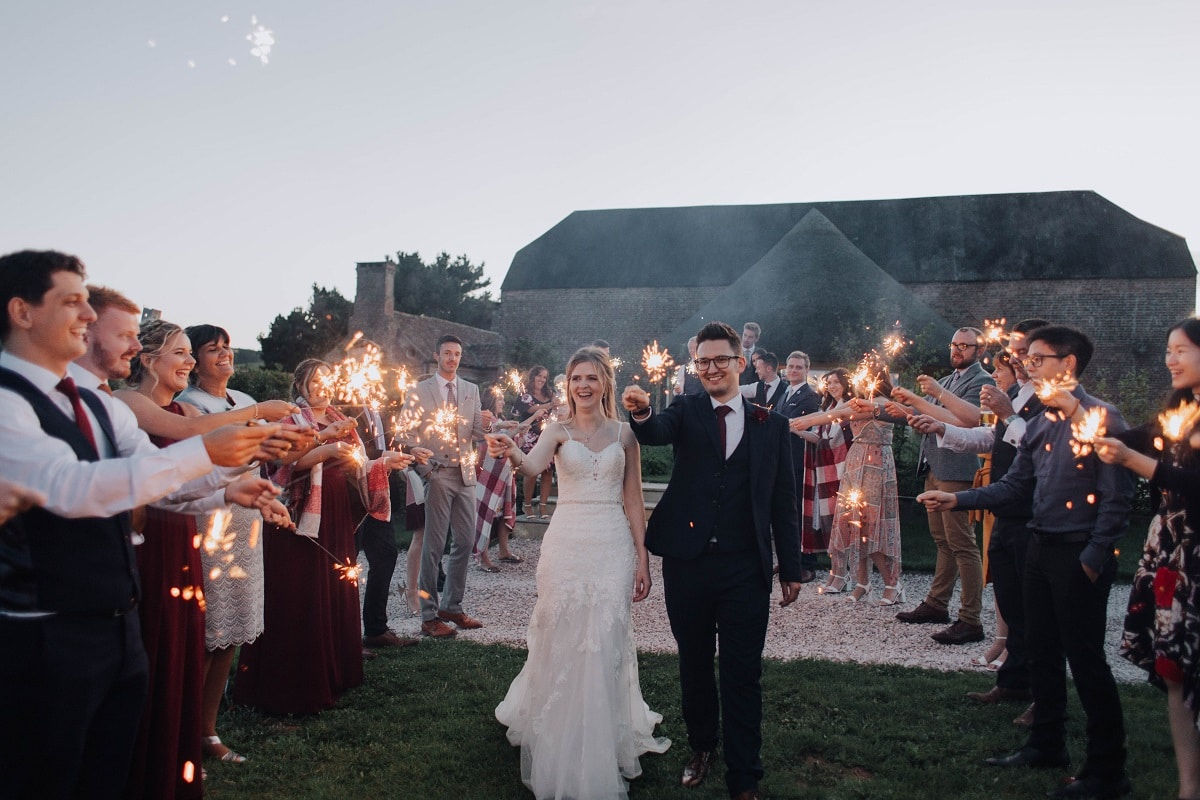 Bride and Groom surrounded by wedding guests all holding sparklers