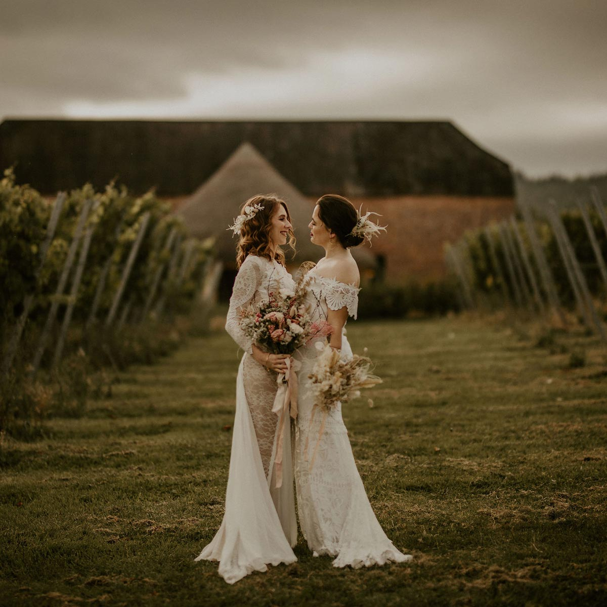 Same sex wedding venue - same sex couple embracing in front of rustic barn