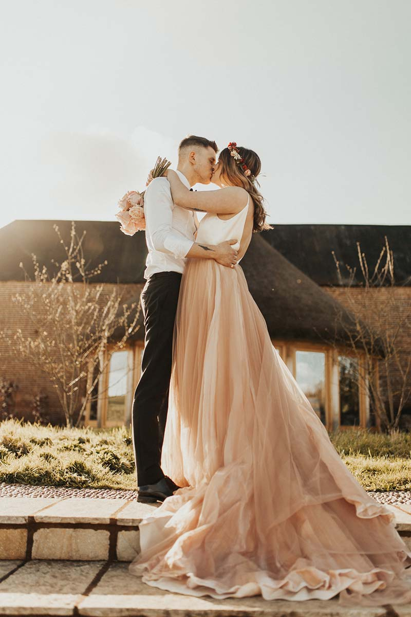 Bride and groom embraced in front of the Round House after their elopement wedding
