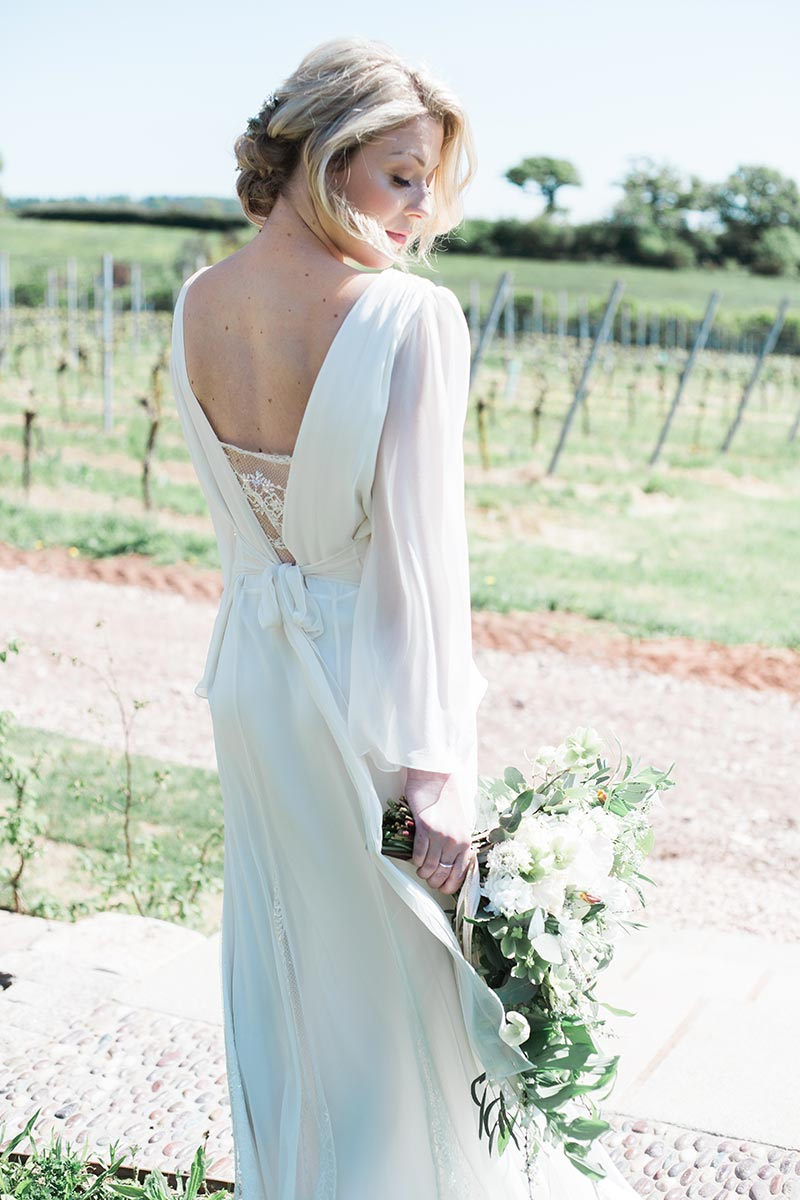 Bride standing on the bridal walk holding a natural flowers bouquet on her small intimate wedding day