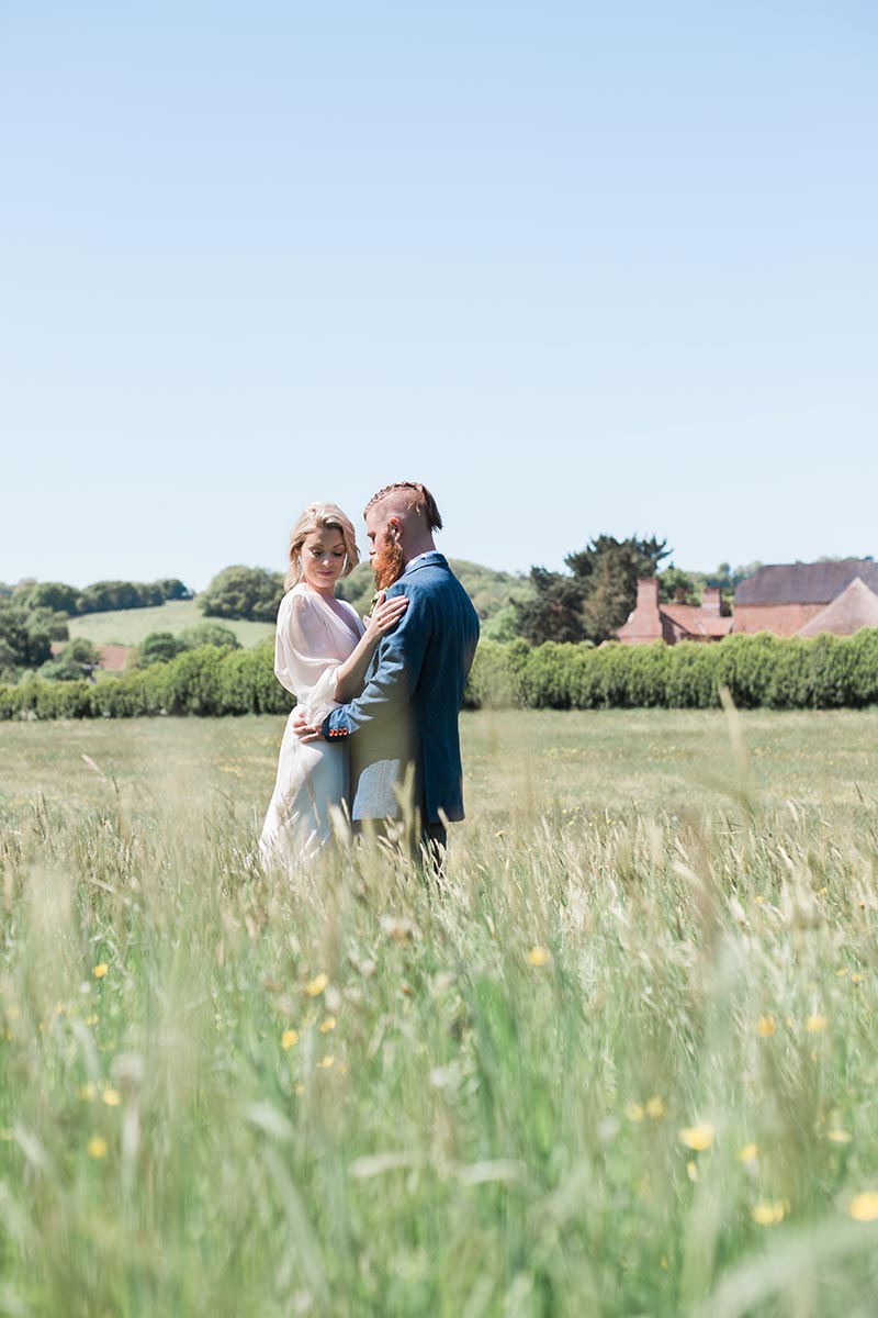 Intimate wedding venue – a couple standing embraced in the wildflower meadow