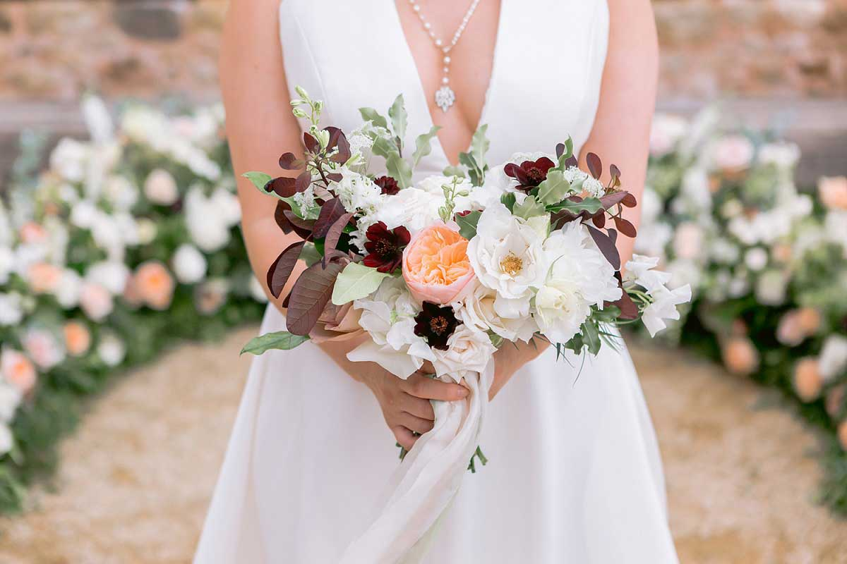 Bride holding mixed flower bouquet