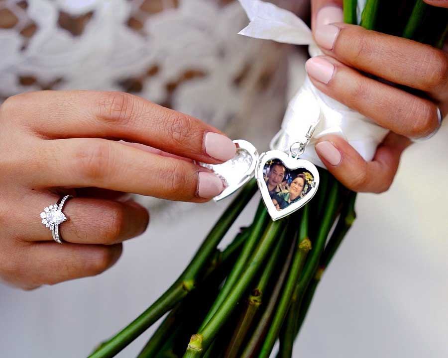 Bride opening heart locket on bouquet