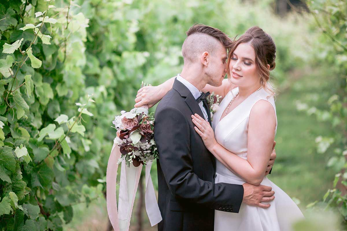 Wedding couple embrace in wild vineyard